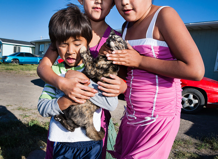 Children pose with an uncooperative kitten. Browning, Blackfeet Reservation, Montana. Backyard, Browning Montana