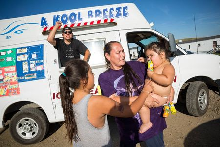 A mother purchases ice cream for daughters on the outskirts of the reservation, in a neighborhood known as FEMA-ville.