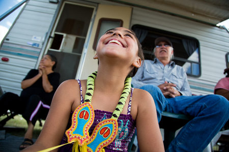 Shawnna Jeminez (age 7)  relaxes with her family after the jingle dance competition at the Heart Butte Pow Wow.