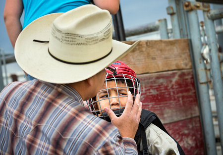 Ethan David readies his terrified son, Josh for the bull riding competition.  David travel from the Canadian side of the reservation for the weekly Youth Rodeo.